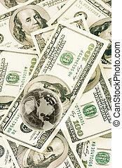 Glass globe on dollar bills pile.