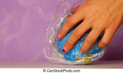 Globe wrapped in plastic wrap. Waste management concept.