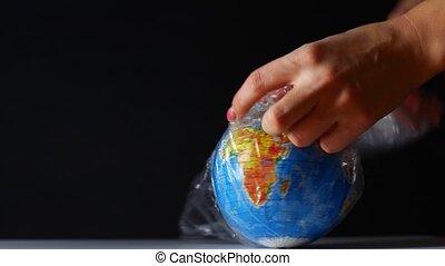 Globe wrapped in polyethylene. Symbolizes delivering...