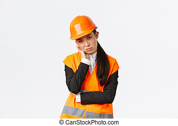 Gloomy and bothered asian female engineer tired of working, wear safety helmet and reflective jacket, lean on palm and looking annoyed at construction manager, listening to boring speech