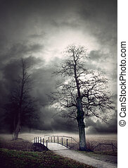 Gloomy autumn landscape with bare tree by a small bridge