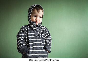 gloomy cute little boy holding hands in pockets