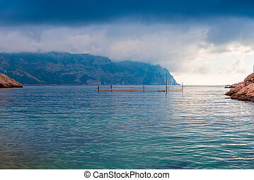 Gloomy dramatic rain clouds over the calm sea and mountains, picturesque landscape