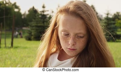 Gloomy face of sad ginger little girl with freckles with...