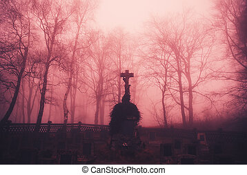 Gloomy forest graveyard with a christian cross in the middle