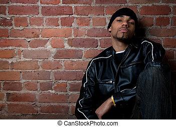Gloomy street guy dressed in black, sitting near a brick wall.