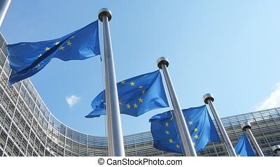 Amazing down up view of EU flags with blue backgrounds and golden stars put in rounds waving in celeste sky at EP house in spring in slo-mo