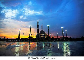 Glorious sunset at Putra Mosque, the principal mosque of Putrajaya, Malaysia, taken after downpour. Seen here reflected of the wet granite of Putra