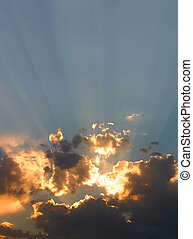 Sun's rays pierce through brightly colored clouds at sunset