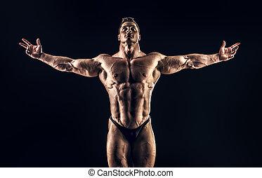 glory of champion - Handsome muscular bodybuilder posing...