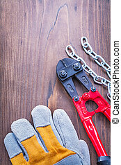 glove chain and steel cutter on vintage wooden board ...