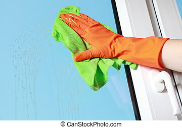 hand in orange glove cleaning window with green rag