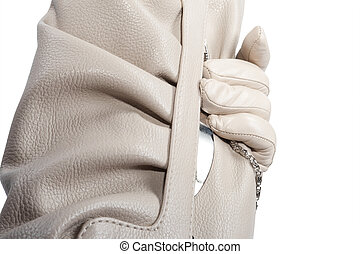gloved hand holding a purse. over white