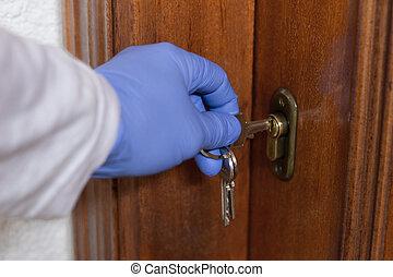 gloved hand opens the house door