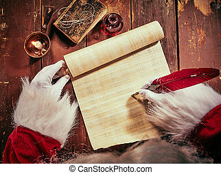 Gloved hands of Father Christmas writing on scroll