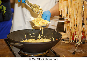 Gloved Hands putting spagetti on a paper plate. Cooking spagetti. Fast food