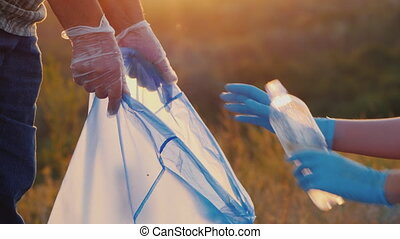 Gloved people scavenge in nature, put bottles in a bag -...