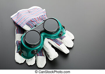 Gloves and protective glasses on grey background