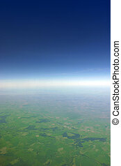 Aerial view of green fields fading away at the horizon line