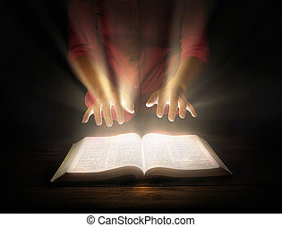 Glowing Bible - A woman holds her hands over a bright ...