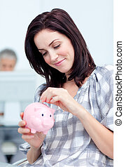 Glowing businesswoman saving money in a piggy-bank at her ...