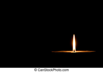 Glowing candle on the dark