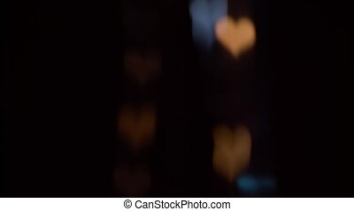 Glowing colorful lights at night in the shape of a heart on a black screen. Bokeh background
