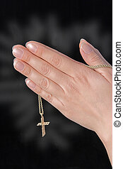Praying hands holding cross, cross glowing