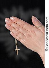 Praying hands holding cross, cross glowing