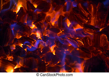 Glowing ember with blue flames - Hot glowing ember in a...
