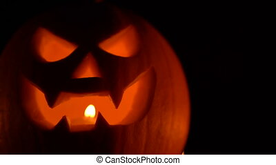 Glowing face with candle light inside in darkness, trick or...