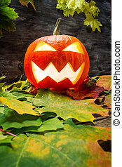 Glowing halloween pumpkin on autumn leaves