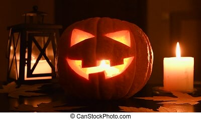 Glowing Halloween pumpkin or Jack o'Lantern on table at home. Candle and lantern on background. All Saints day. Seamless loop