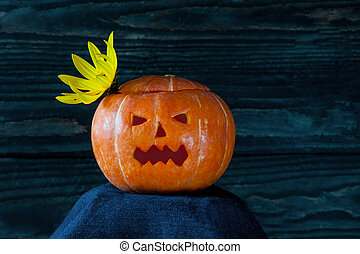 Glowing Halloween pumpkin with yellow flower in the shape of a crown on a dark background.