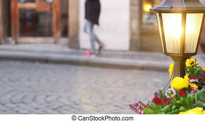 Glowing lantern and flower bed against tourists, beautiful...