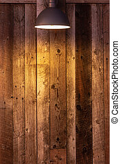 Glowing light bulb on wooden background. Light falling from old vintage lamp on wall.