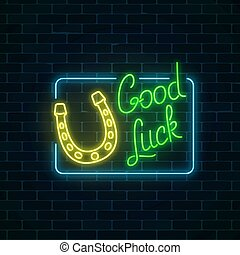 Glowing neon sign with good luck wish and horseshoe in rectangle frame on dark brick wall background.