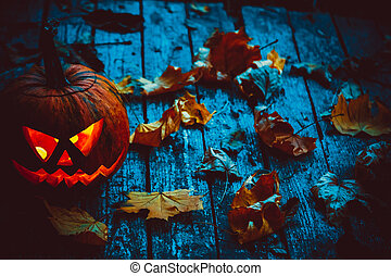 Glowing pumpkin symbolizing the head of old Jack, with autumn leaves on wooden background. Soft focus. shallow DOF