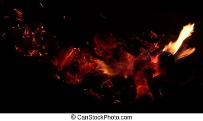 Glowing red embers are stirring in the dark.