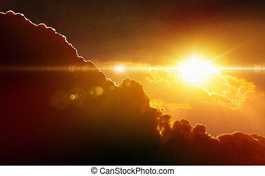 Glowing sunset, dark red clouds, bright sun rays