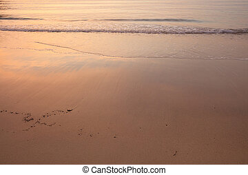 Glowing sunset in ocean. Sky reflecting in water and sand