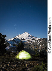 Glowing tent beneath moonlit Mount Baker, Washington state Cascades