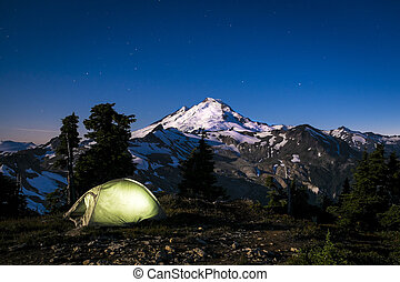 Glowing tent at night beneath Mount Baker, Washington state...