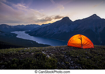 Glowing tent set up on a ridge for camping in the mountains