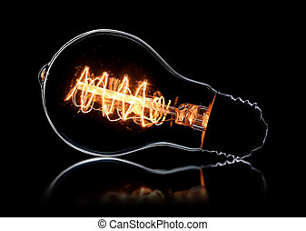 Glowing vintage light bulb on black