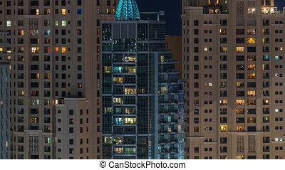 Glowing windows in multistory modern glass residential...