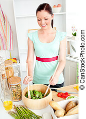Glowing young woman preparing salad at home