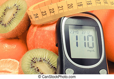 Glucometer, fresh fruits with tape measure and glass of juice