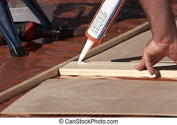 Worker using a glue gun