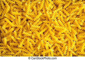 Full frame food background of colorful yellow spiral gluten-free corn and rice fusilli pasta used as an ingredient in Mediterranean cuisine for people with a gluten allergy